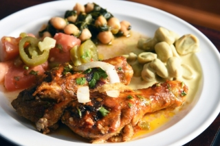 A plate of grilled chicken, tomato-jalapeno salad, chickpeas with spinach and green fava beans