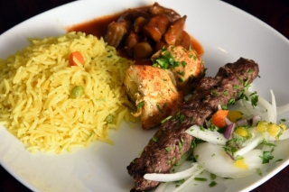 A plate of beef and chicken kabobs, seasoned rice and stewed okra