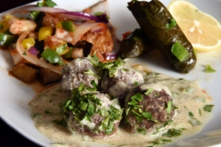 A plate of meatballs in tahini sauce, stuffed grape leaf and musakaa