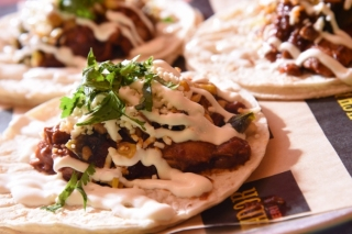 El Taco Luchador's Mole taco with braised chicken, roasted corn-poblano, crema, and queso fresco